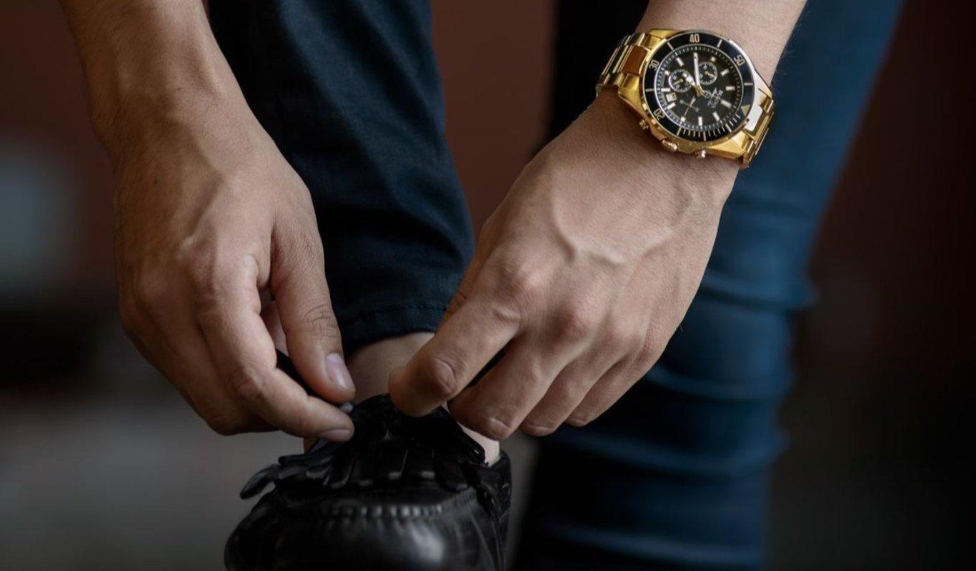 Un hombre se ata los zapatos con un reloj de lujo. (Foto: Unsplash)