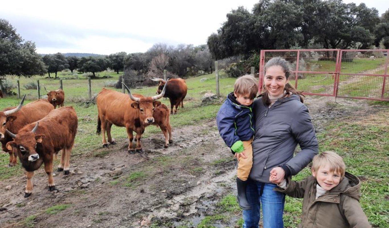 María Gómez, junto a sus hijos, en la finca de Fresnedillas donde cría su ganado.
