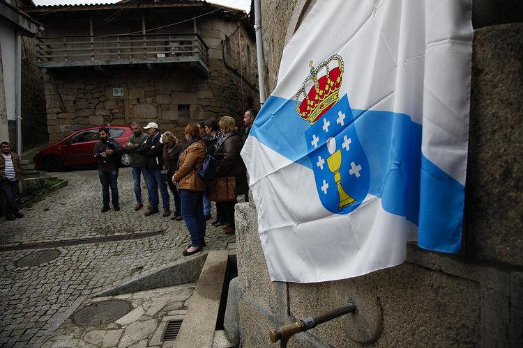 Políticos locales y vecinos, junto a la fuente, tapada con la bandera gallega.