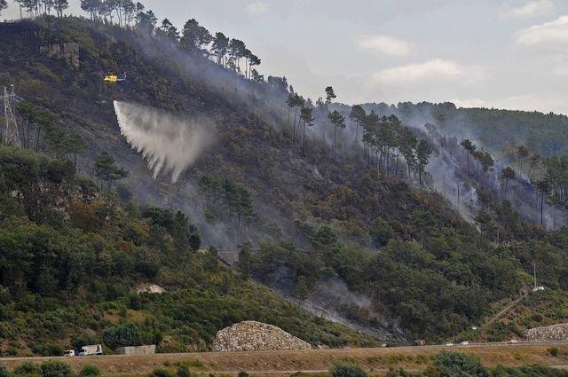 Una aeronave descarga agua sobre las llamas, muy cerca de la autovía AG-53.