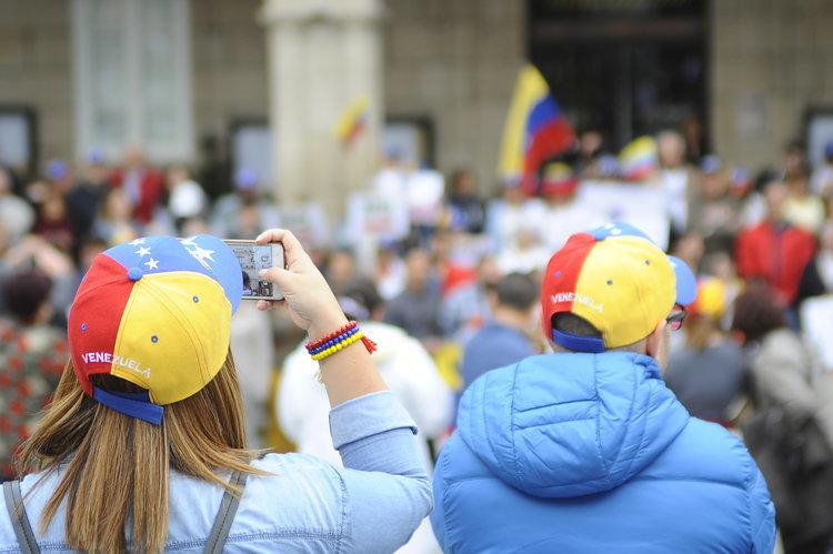 Dos personas graban una de las últimas manifestaciones de venezolanos en la ciudad.